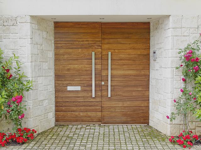 Porte d'entrée contemporaine en bois avec mur en pierre