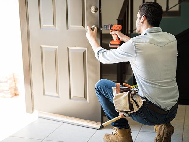 Serrurier avec visseuse qui travaille sur une porte d'entrée