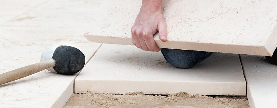 Pose dalle pierre reconstituée sur lit de sable