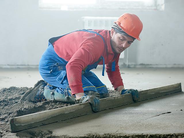 Ouvrier lissant une dalle béton