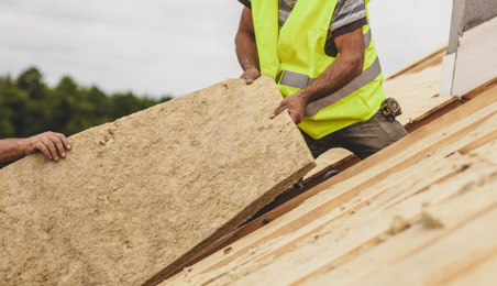 Couvreur installant un panneau d'isolant sur un toit