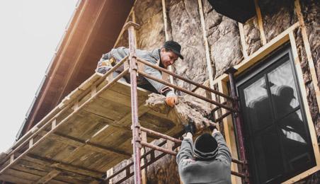 Deux ouvriers sur un échafaudage en train de poser de la laine de roche en façade