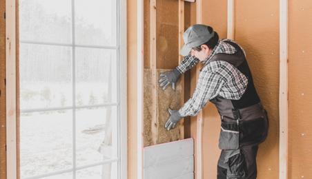 Ouvrier posant des panneaux d'isolant thermique à l'intérieur d'une maison