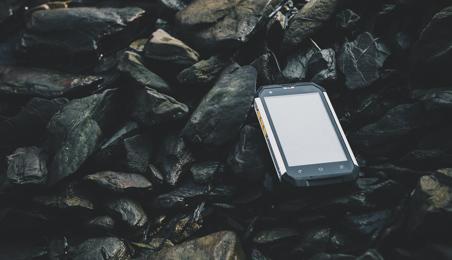 Smartphone avec coque de protection renforcée sur des galets noirs