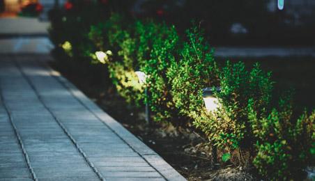 Allée de jardin la nuit, avec éclairage par lanternes dans des buissons