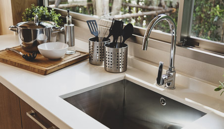 Evier de cuisine en inox sur plan de travail en résine, pots à ustensiles en inox, robinet col de cygne chromé