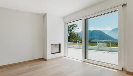 Grande baie vitrée en PVC blanc ouvrant sur une terrasse