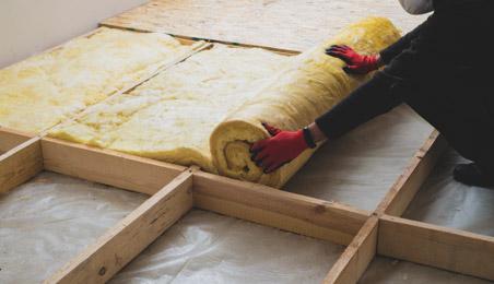 Ouvrier déroulant un isolant sur un plancher en bois