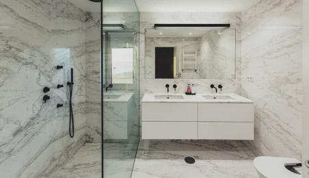 Salle de bain en marbre blanc, meubles laqués blanc, douche à l'italienne