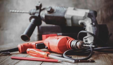 Perceuse rouge et perforateur gris posés sur un plancher