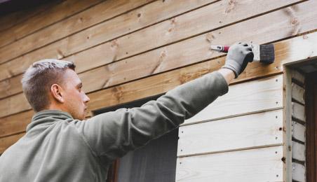 Homme passant de la lasure sur une façade en bois