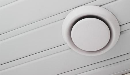 Bouche de VMC sous un plafond en lambris blanc