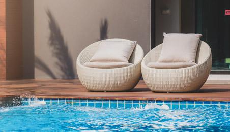 Deux fauteuils boule blanc avec coussin au bord d'une piscine