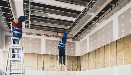 Ouvriers posant des rails pour installer des plaques de plâtre au plafond