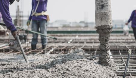 Ouvriers coulant du béton sur une armature de plancher en acier