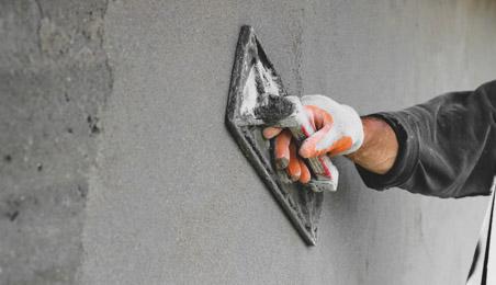 Main d'un ouvrier en train de lisser un enduit sur un mur en béton
