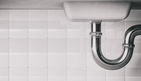 Siphon chromé sous un lavabo blanc
