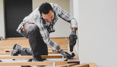 Ouvrier posant des lames de terrasse en bois