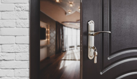 Poignée en métal sur une porte en bois foncé, clés dans la serrure