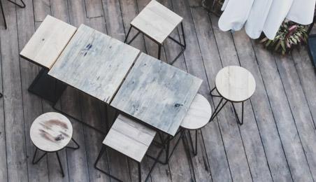 Terrasse en bois vieilli avec ensemble de tables et tabourets