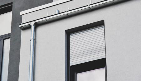 Volet roulant en partie abaissé sur une façade moderne en béton