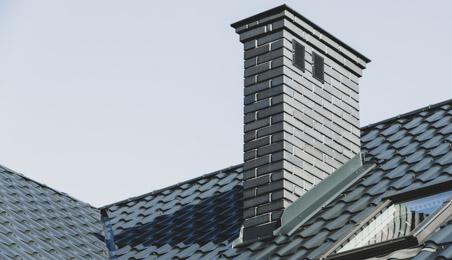 Abergement en métal gris au pied d'une cheminée sur un toit de tuiles béton grises