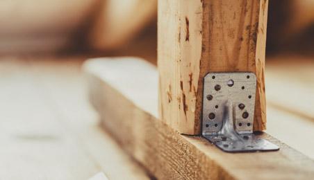 Equerres en métal galvanisé fixée au pied d'une poutre de charpente
