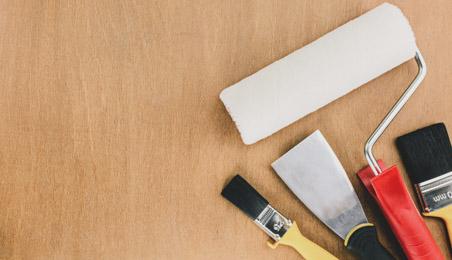 Pinceaux et rouleaux pour la peinture posé sur une surface en bois