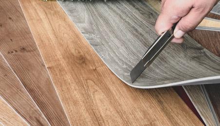 Lame de sol PVC coupée par un artisan avec un cutter