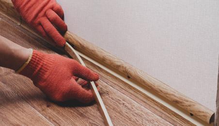 Artisan posant un joint vinyle sous un quart de rond, sol teinte bois naturel