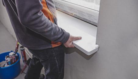 Ouvrier installant un appui de fenêtre en béton