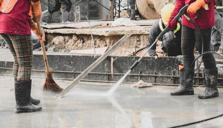 Ouvriers nettoyant un sol avec un jet haute pression et un balai