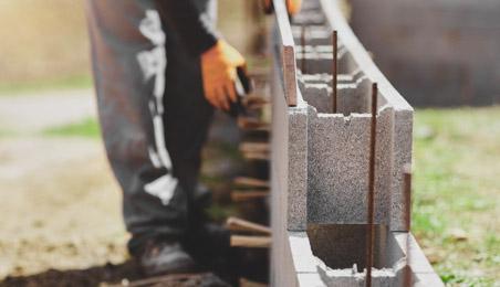 Ouvrier construisant un mur en parpaings