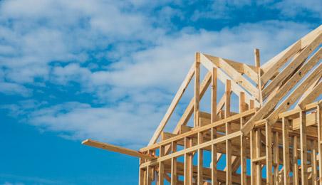 Ossature et charpente de maison en bois sur fond de ciel bleu