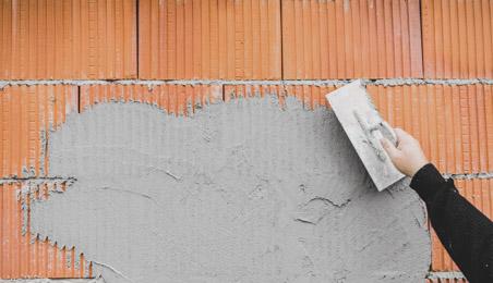 Maçon posant un enduit sur un mur de briques plâtrières
