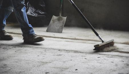 Ouvrier balayant un sol en béton