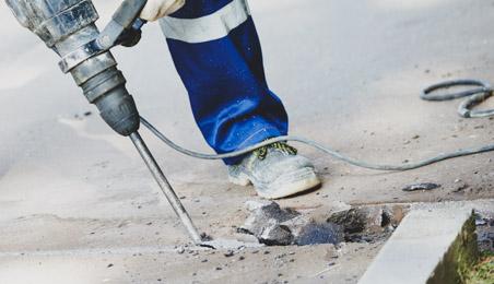 Ouvrier attaquant un sol en béton avec un perforateur