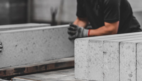 Ouvrier poussant un carreau de béton cellulaire