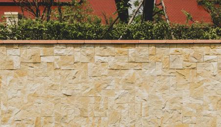 Chaperon de mur en terre cuite sur un mur en briques claires