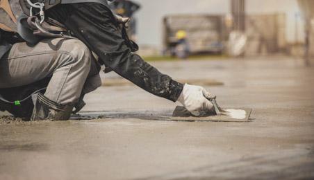 Ouvrier talochant du béton sur une chape
