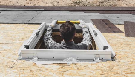 Couvreur posant un châssis de fenêtre de toit