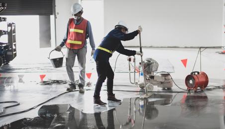Ouvriers passant une couche imperméabilisante sur un sol béton
