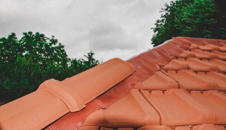 Closoirs de faîtage rouges sur un toit en tuiles terre cuite rouge plates