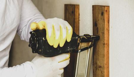 Ouvrier utilisant un cloueur pour fixer un montant en bois