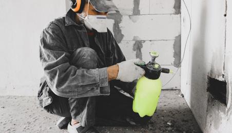Ouvrier manipulant un pulvérisateur en plastique jaune