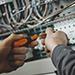 Electricien intervenant sur un boîtier électrique