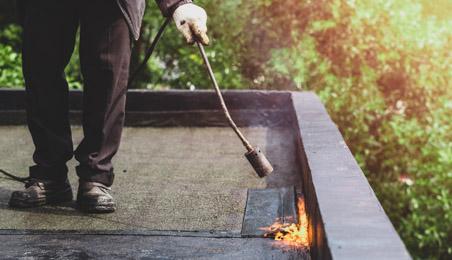 Couvreur fixant une bande d'étanchéité bitumeuse au chalumeau sur un toit terrasse