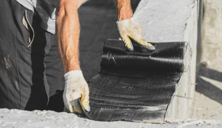 Maçon posant une feuille d'étanchéité sur une fondation