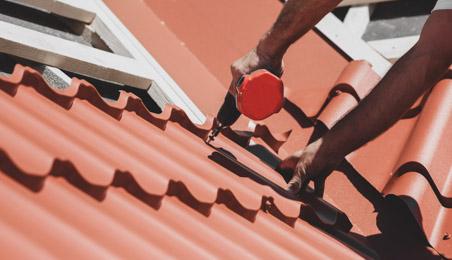 Couvreur fixant une plaque de toit aspect tuile avec une visseuse