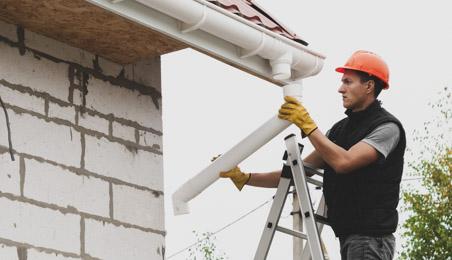 Ouvrier installant une descente PVC sous une gouttière PVC blanc sur une maison en construction